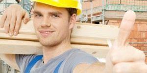 Bild eines Bauarbeiters, der einen gelben Schutzhelm mit seinem Daumen oben trägt